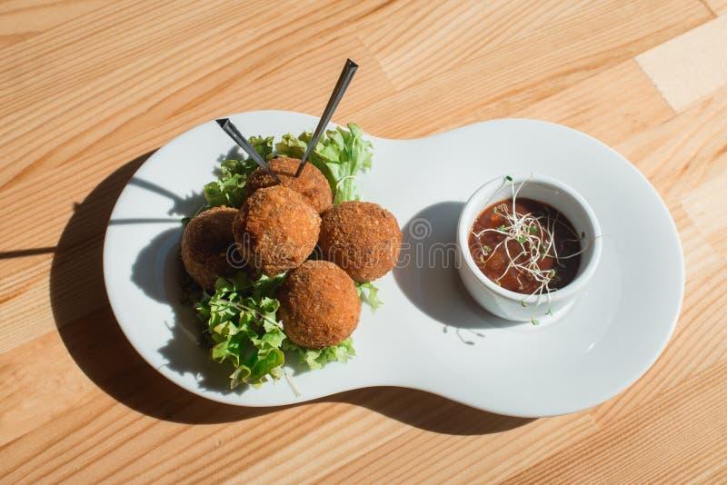Le plan rapproché du plat avec les croquettes espagnoles a servi avec de la salade et la sauce photos libres de droits