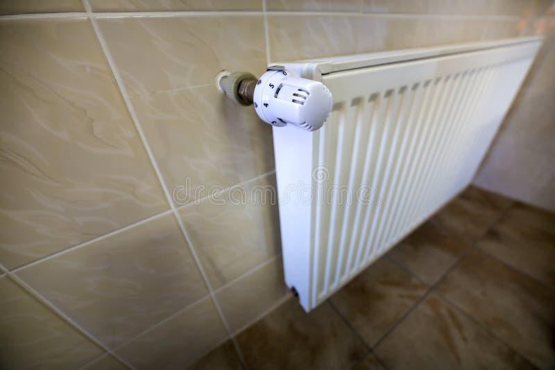 Le plan rapproché du radiateur de chauffage blanc avec l'ion de valve de thermostat a couvert de tuiles les murs et le fond de pl photos stock