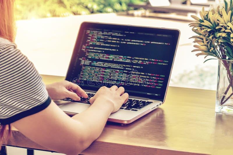 Le plan rapproché du ` s de programmeur remet travailler sur des codes sources au-dessus d'un ordinateur portable un jour ensolei photos stock