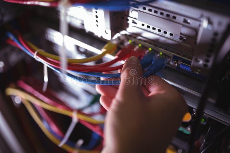 Le plan rapproché du technicien branchant le câble de correction dans un support a monté le serveur photographie stock libre de droits