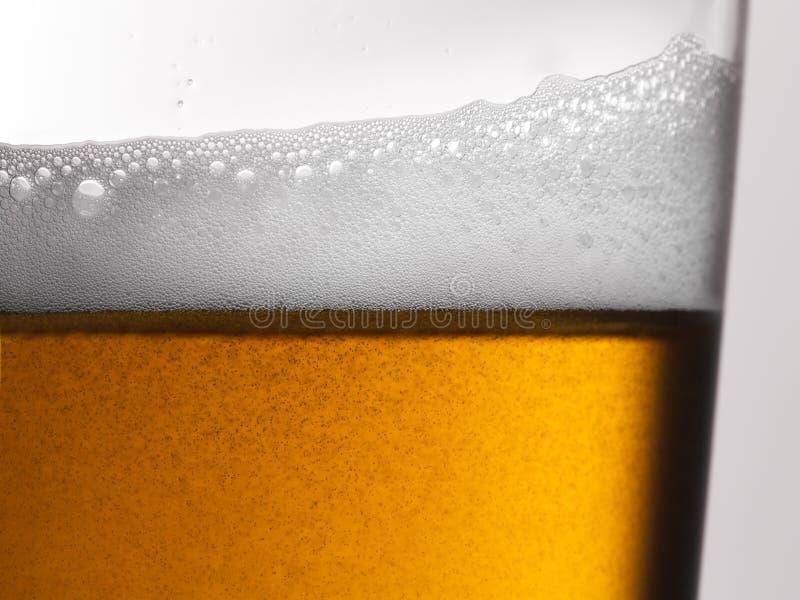 Le plan rapproché du verre de bière fraîchement versé avec la tête et la carbonation écumeuses bouillonne photographie stock libre de droits