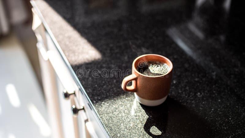 Le plan rapproché large a concentré le tir d'une tasse de café noir sur une étagère de cuisine pendant le matin images libres de droits