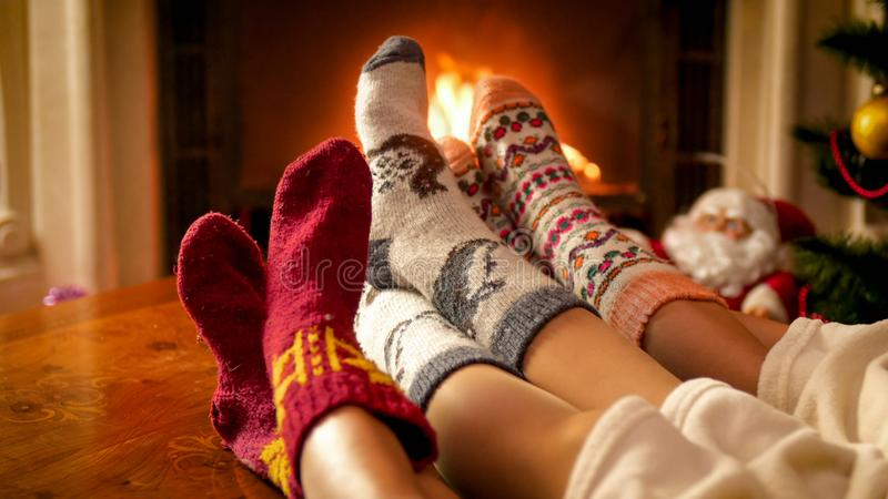 Le plan rapproché a modifié la tonalité l'image de la famille dans les chaussettes tricotées chauffant par le coin du feu le réve images libres de droits