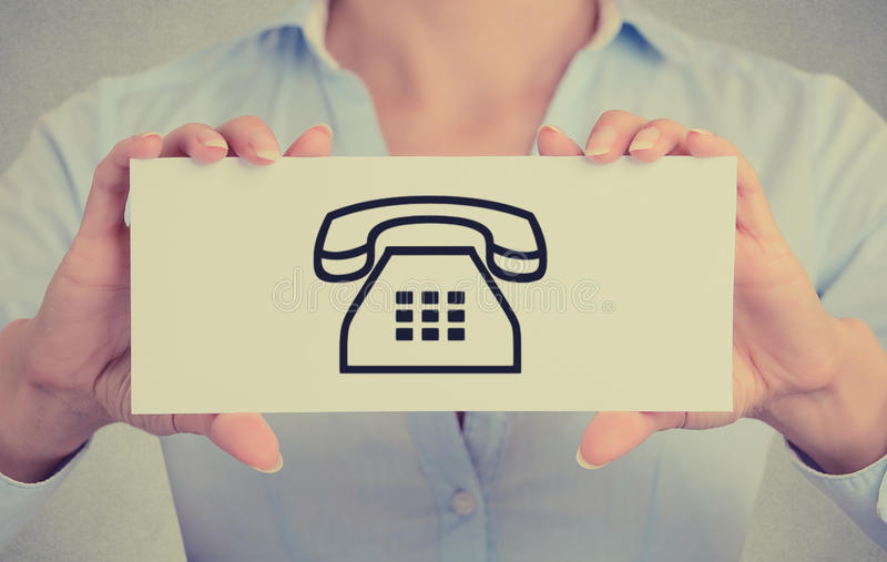 Le plan rapproché remet tenir le signe de carte avec l'icône de contact téléphonique photo libre de droits