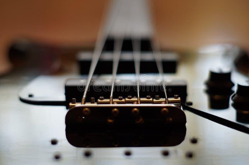 Le plan rapproché a tiré d'un pont en guitare basse - pont de style de Jazz Bass d'amortisseur photographie stock libre de droits