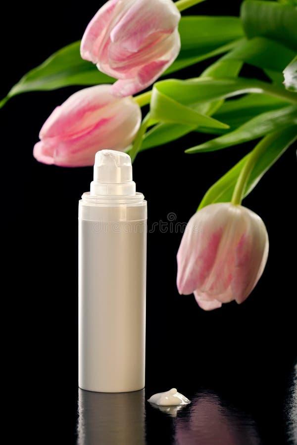 Le plan rapproché a tiré de la crème/de lotion et de tulipes faciales photos libres de droits