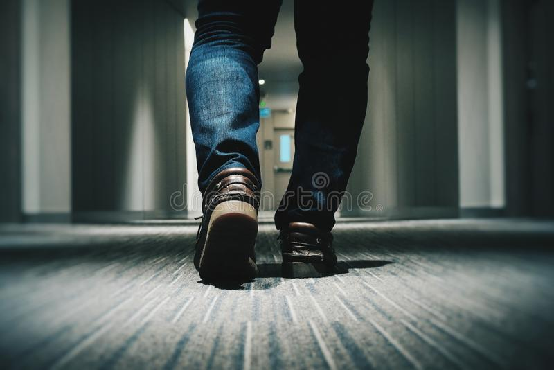 Le plan rapproché a tiré des jeans de port d'un mâle et de la marche dans un couloir - fond frais image libre de droits