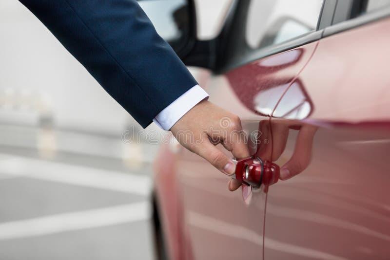 Le plan rapproché a tiré du jeune homme d'affaires tirant la poignée de portière de voiture photographie stock libre de droits