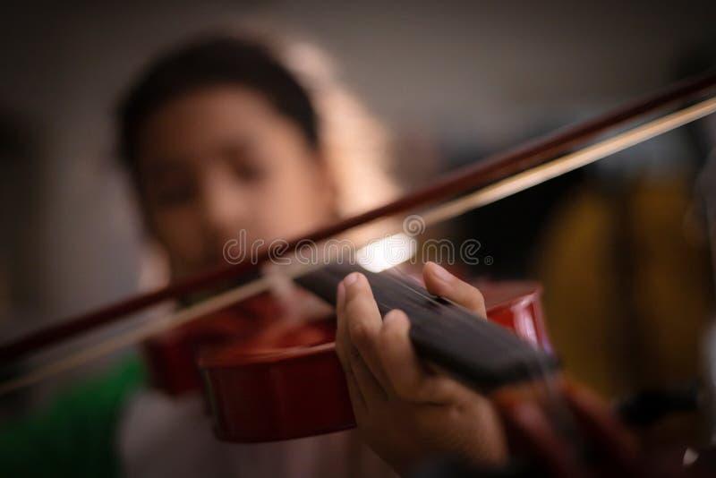 Le plan rapproché a tiré peu de fille jouant l'orchestre de violon instrumental avec le ton de cru et l'obscurité et le grain d'e photographie stock libre de droits