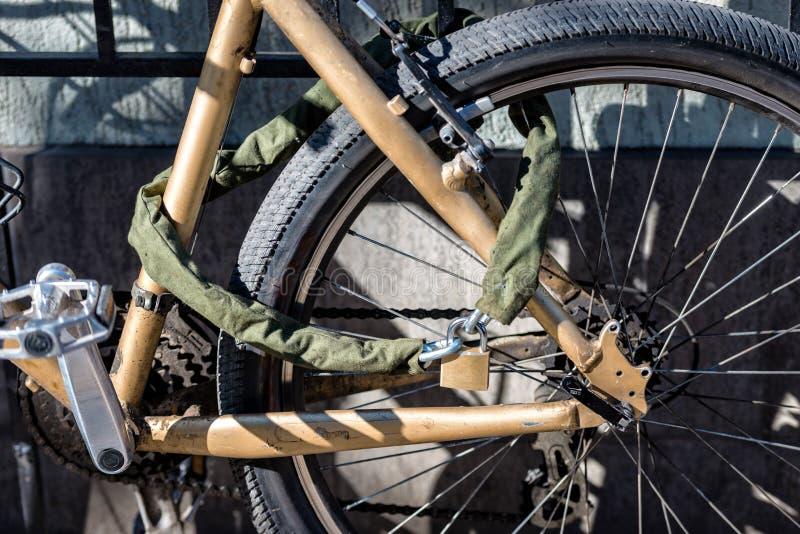 Le plan rapproché un vieux cycle a été fermé à clef par un casier avec des tiges en métal à photos stock