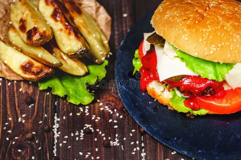 Le plan rapproch? de l'hamburger fait ? la maison de boeuf avec de la laitue et la pomme de terre a servi sur la planche ? d?coup images libres de droits