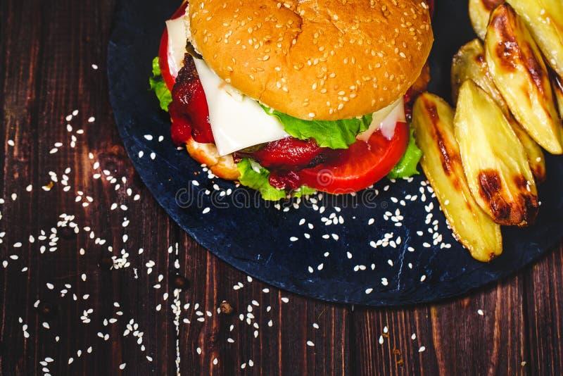 Le plan rapproch? de l'hamburger fait ? la maison de boeuf avec de la laitue et la pomme de terre a servi sur la planche ? d?coup photographie stock
