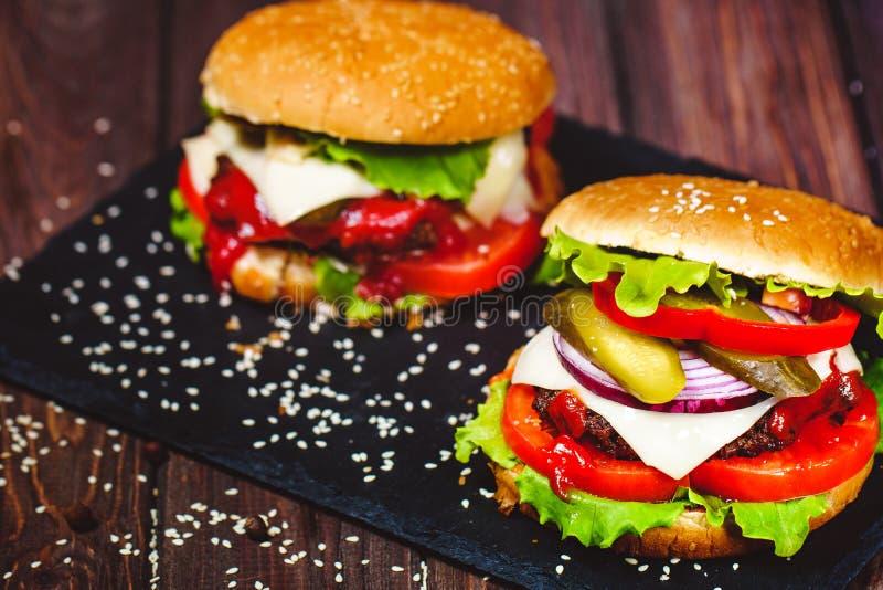 Le plan rapproch? de l'hamburger fait ? la maison de boeuf avec de la laitue et la pomme de terre a servi sur la planche ? d?coup images stock