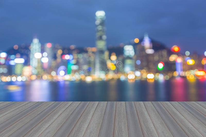 Le plancher en bois s'ouvrant, nuit de ville allume la vue, bokeh brouillé image libre de droits