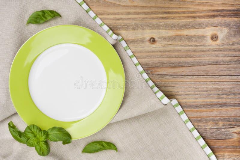 Le plat avec le basilic part sur la table en bois avec le fond de nappe photographie stock