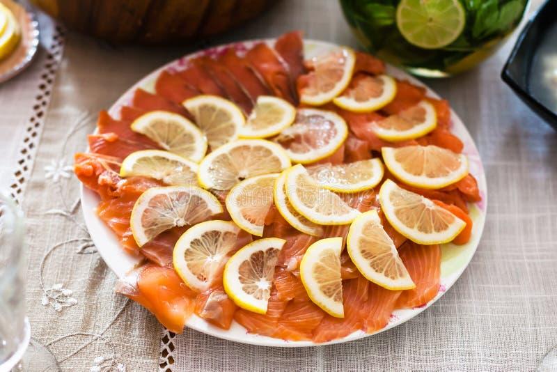 Le plat avec les saumons fumés découpés en tranches pêchent avec le citron photo libre de droits
