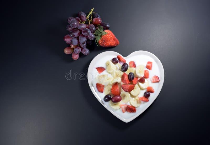 Le plat crème en forme de coeur rempli du yaourt avec des tranches de banane, fraises a coupé en morceaux et baies de raisin photos libres de droits