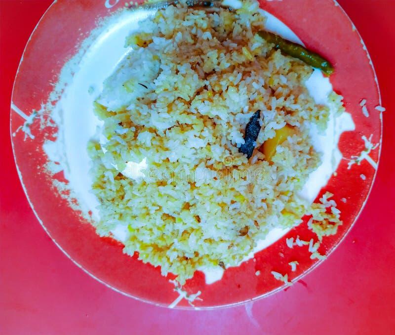 Le plat de Fried Pilaf ou de riz de pilaf a servi dans un plat rouge de mélamine sur un Tableau rouge photographie stock