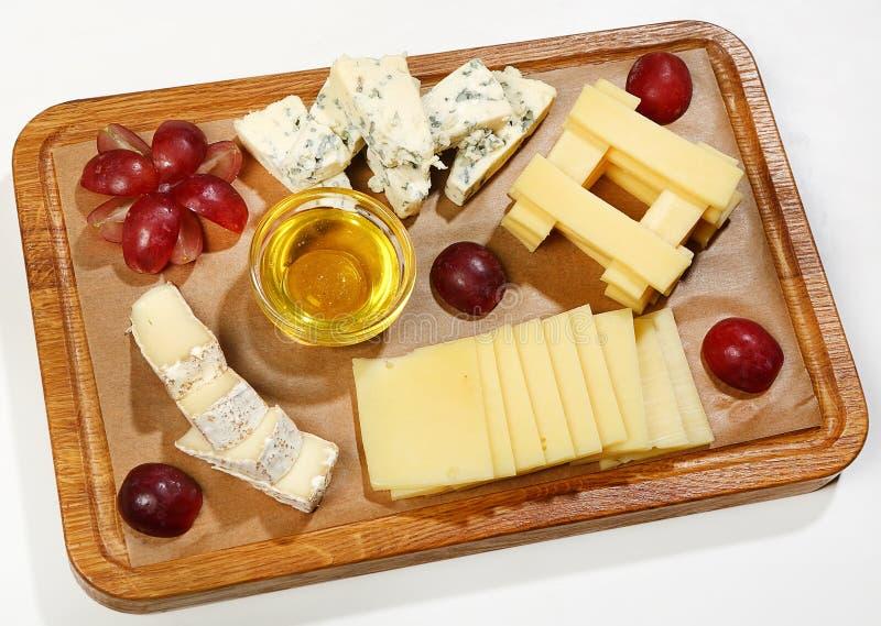 Le plat de fromage - camembert, fromage de Dorblu, parmesan, cheddar, Néerlandais, a servi avec des raisins, le miel et des noix photographie stock