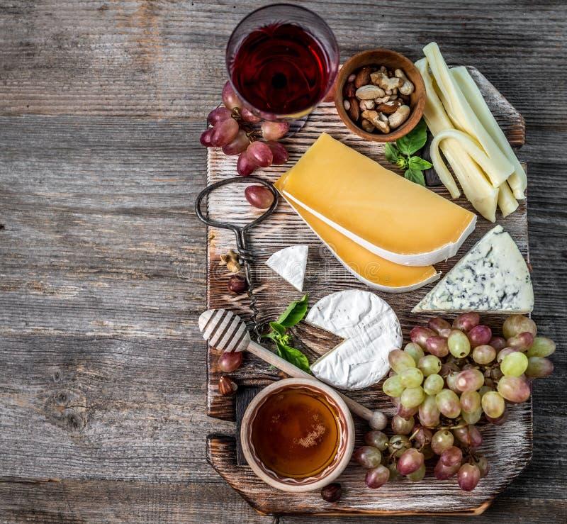 Le plat de fromage a servi avec du vin, les écrous et le miel images stock