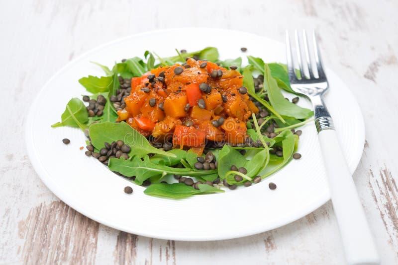 Le plat de la salade avec l'arugula, les lentilles noires et le légume cuisent photo libre de droits