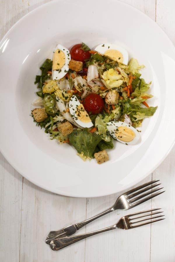Le plat de salade avec des croûtons, tomates-cerises, oeuf à la coque divise a photo stock