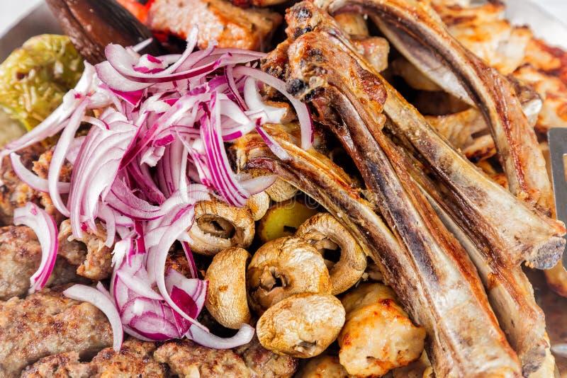 Le plat de viande avec les morceaux de viande délicieux, nervures, a grillé des pommes de terre et des champignons à l'oignon Fer photos libres de droits