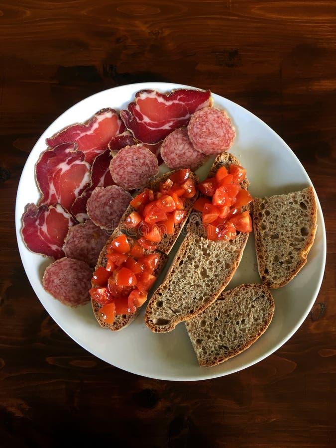 Le plat de viande froide de plateau d'Antipasto avec le prosciutto de pain coupe en tranches le salami et la tomate à l'arrière-p photos stock