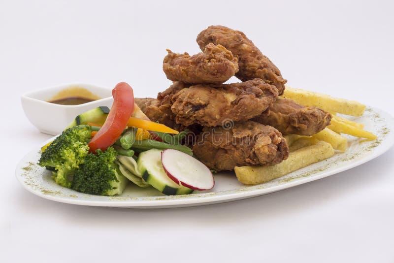 Le plat des ailes et de la salade de poulet, servi avec la passiflore comestible de passiflore épicée garnissent et font frire de images stock