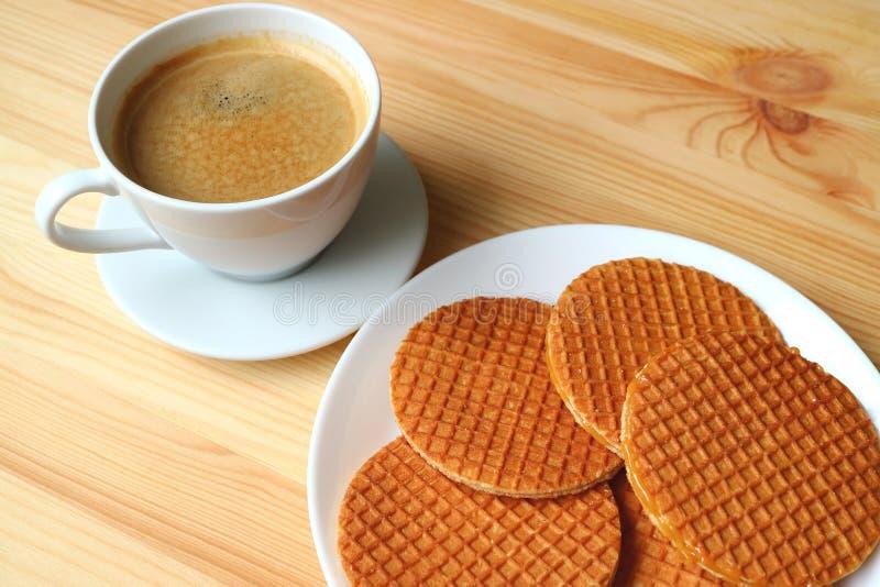 Le plat des biscuits de Stroopwafel, les bonbons traditionnels néerlandais savoureux a servi sur la table en bois avec une tasse  images libres de droits