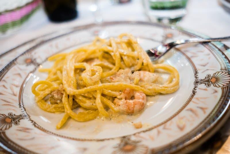 Le plat des spaghetti italiens de nourriture un carbonara de La donnent sur le tir photos libres de droits