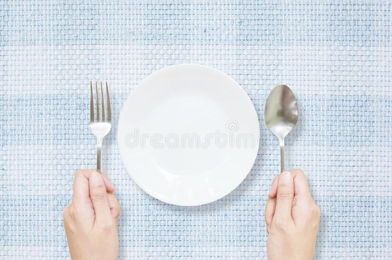 Le plat en céramique blanc de plan rapproché avec la fourchette inoxydable et la cuillère chez la main de la femme sur le tapis b photo stock