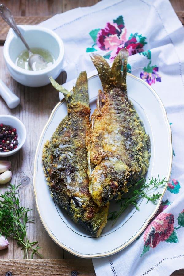Le plat moldove ou roumain traditionnel, les poissons frits dans le panage de maïs a servi avec de la sauce à ail Type rustique photos stock