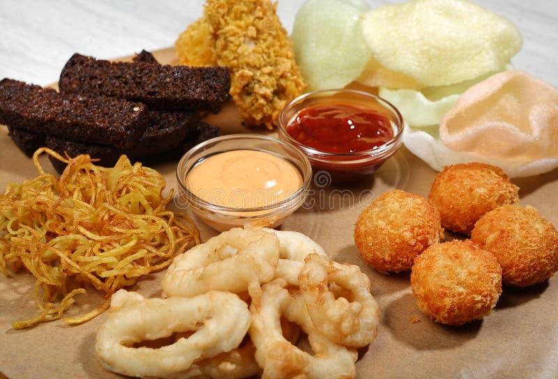 Le plat-poulet de bière s'envole, crevette et pommes chips, croûtons de seigle, boules de fromage, anneaux de calmar, sauces barb images stock