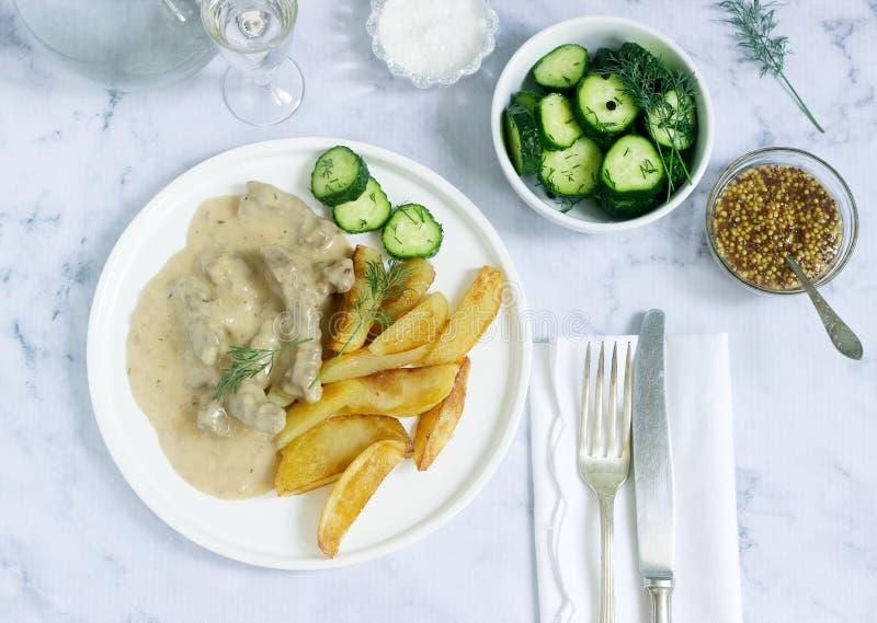 Le plat russe traditionnel de boeuf stroganoff du boeuf en sauce, servi avec les pommes de terre frites, a mis en boîte des conco image stock