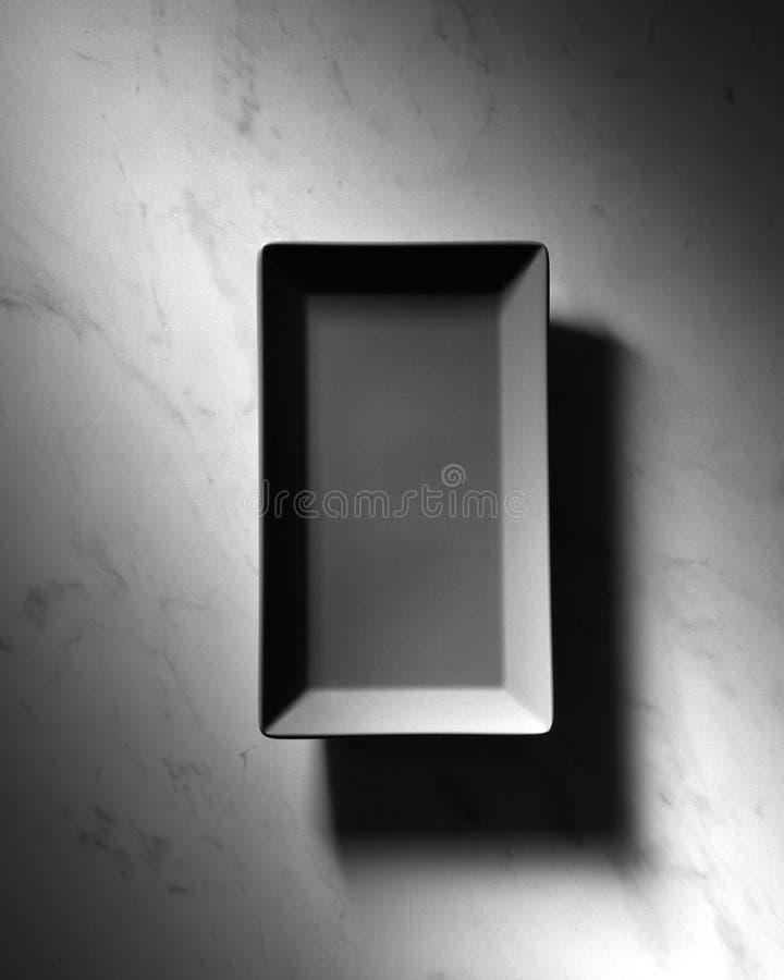 Le plat vide rectangulaire noir a présenté sur un fond de marbre gris avec des ombres, l'espace pour le texte Vue supérieure photos stock