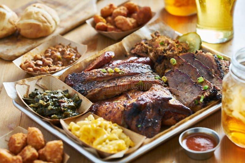 Le plateau de BBQ de style du Texas avec la poitrine fumée, nervures de St Louis, a tiré le porc, le poulet, les sites branchés,  image libre de droits