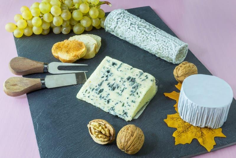 Le plateau français de fromage avec des raisins sont sur une ardoise image stock