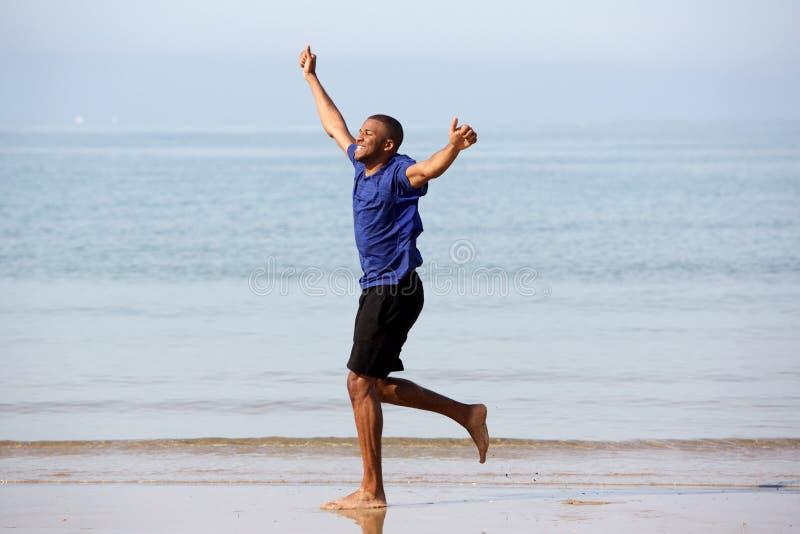 Le plein corps a excité le type africain courant sur la plage avec des bras augmentés image libre de droits