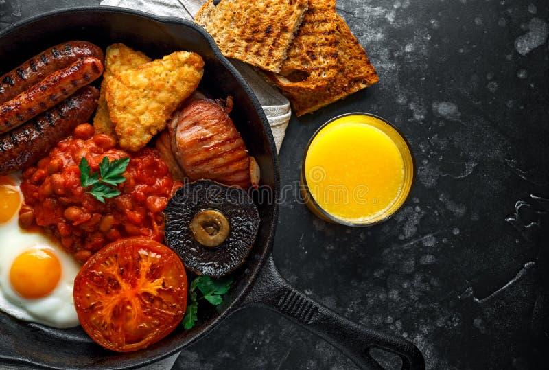 Le plein petit déjeuner anglais avec le lard, saucisse, oeuf au plat, a fait des haricots, des pommes de terre rissolées et des c photo stock