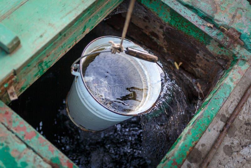 Le plein seau de l'eau claire est sorti d'un puits profond image libre de droits