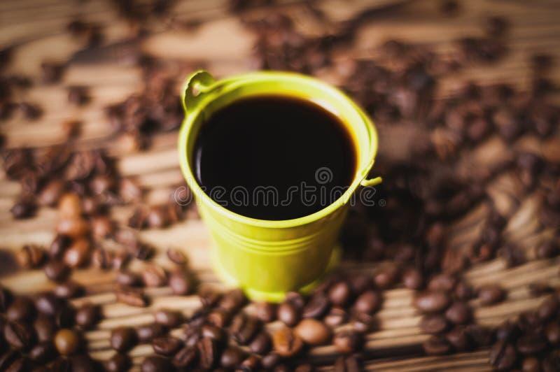 Le plein seau vert en métal de café noir près a dispersé le sort de haricots rôtis image libre de droits