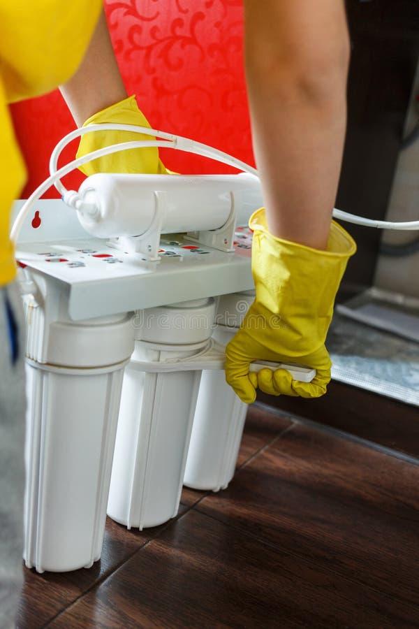 Le plombier dans les changements jaunes de gants de m?nage arrosent des filtres D?panneur installant des cartouches filtrantes de photographie stock
