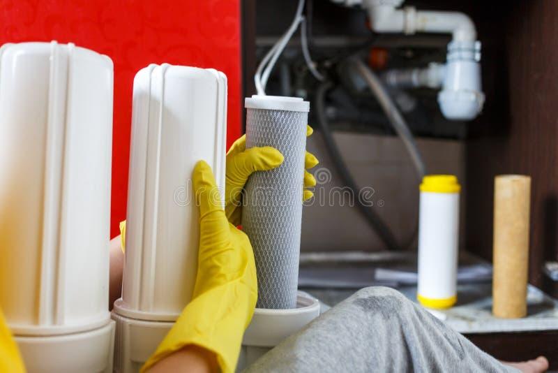 Le plombier dans les changements jaunes de gants de m?nage arrosent des filtres D?panneur installant des cartouches filtrantes de photos libres de droits