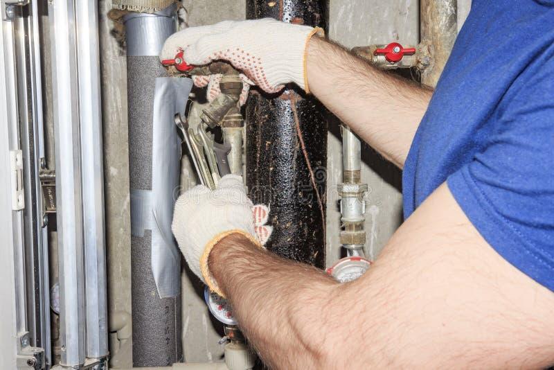 Le plombier dans les gants blancs avec des clés répare les tuyaux dans l'unité de tuyauterie Réparation des tuyaux, valves, mètre image stock
