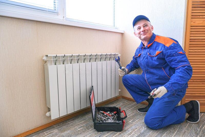Le plombier masculin fixe une fuite La clé réglable serrer les joints de brides d'écrou, isolats images stock