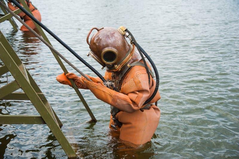 Le plongeur immerge dans un costume de plongée de mer profonde de vintage images libres de droits