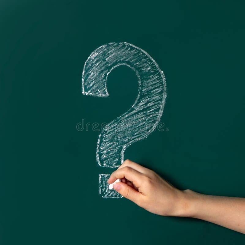 Le point d'interrogation est dessiné dans la craie blanche sur un tableau vert Pi?ce fra?che Les mains de l'enfant écrivent un po images libres de droits