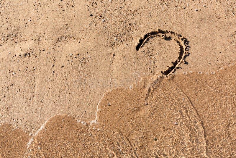 Le point d'interrogation se connectent la plage de sable pr?s de la mer Concept de dilemme, de r?ponse et de question photo libre de droits