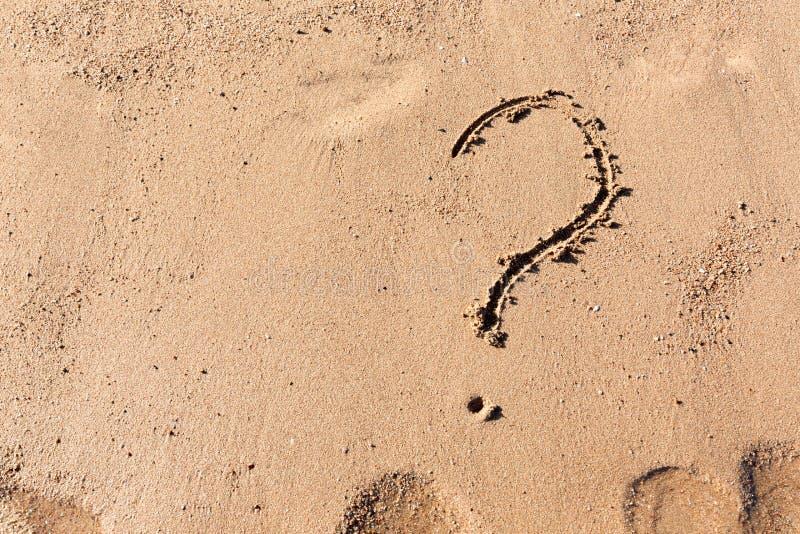 Le point d'interrogation se connectent la plage de sable pr?s de la mer Concept de dilemme, de r?ponse et de question images stock